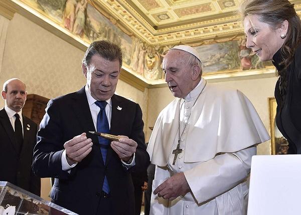 El Papa Francisco escucha la explicación que le hizo el Presidente Santos sobre el balígrafo que se creó como símbolo de la paz en Colombia.