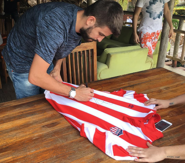 Piqué estampa su firma en una camiseta del Junior a un fan