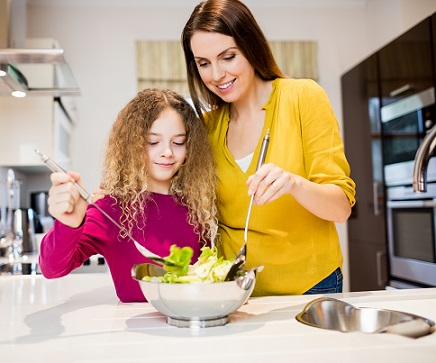 Mother assisting daughter in making salad in kitchen